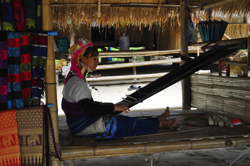 A Karen woman weaving silk scarves, Thailand