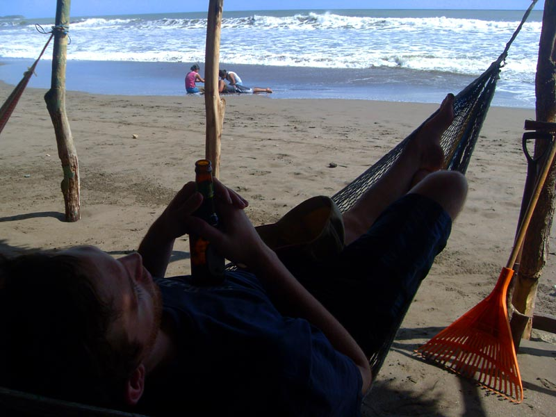 Rowan enjoying a beer and hammock with a beach view in La Boquita